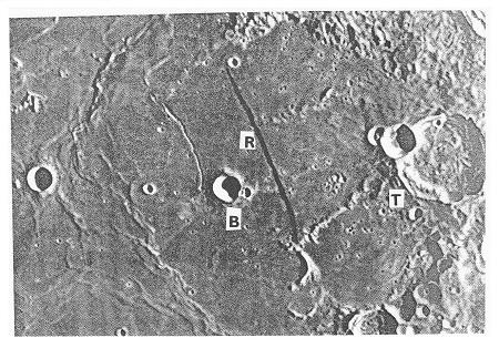 Obr. 9: Rupes Recta (Přímá stěna, R), na západ od kráteru Thebit (T) (dříve Delanuay) a od kráteru Birt (B) vzdálený o 2 jeho průměry na SV. P. m. B.